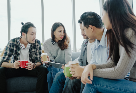 team-holding-coffee-cups-and-discussing-ideas-in-o-48MMM75.png